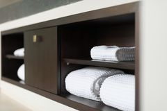 Rolled white towels on shelf in hotel bathroom. Royalty Free Stock Image