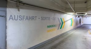 On the wall of a car park is written in German French and Englis Stock Photography
