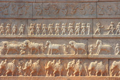 Wall with a carved relief: the Indian army. Wall with a carved relief: big ancient Indian army with horses and elephants Royalty Free Stock Images