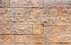 Wall with a carved relief: scenes of hunting and life Royalty Free Stock Photo