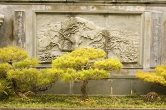 Wall carving. Wall decorated with a Chinese carving of trees with bonsais in the foreground Stock Photos