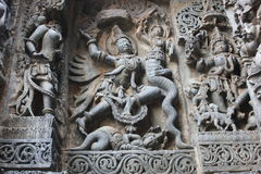 Hoysaleswara Temple wall carved with sculpture of Garuda humanoid bird fighting with Nagas Serpents Royalty Free Stock Photo