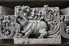 Hoysaleswara temple wall carving of Makara mythical animal carrying lord Varuna god of rain and his wife. This is a wall carving of Makara mythical animal Stock Photos