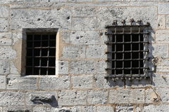 Wall of a castle with barred window. Old grey stone wall with rusty sturdy bars in front of a window Royalty Free Stock Images