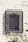 Wall of a castle with barred window. Old grey stone wall with rusty sturdy bars in front of a window Stock Photos
