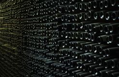 Wall of the cellar full of old wine bottles stock photography