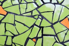 Wall from ceramic pieces green and orange color for background. Stock Photo
