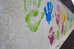 Wall with children hand prints. Wall with children colorful hand prints royalty free stock images