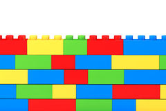 Wall from children plastic blocks. On a white background Royalty Free Stock Photography