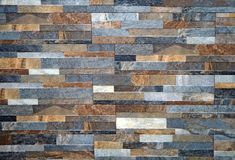 Wall cladding for interiors made of natural stones strips with different sizes. Colors are gray,brown and white. stock images