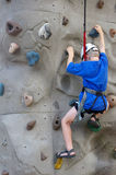 Wall climber. Boy climbing a wall stock photography