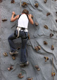 Wall Climbing. Young lady climbs a wall Stock Photo