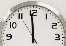 Wall Clock. A modern wall clock showing five seconds until midnight. Time is running out Royalty Free Stock Photos