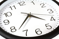 Wall Clock. Closeup of black and white wall clock with three hands isolated over white Stock Photography