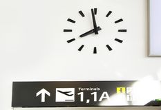 Wall clock at an airport with navigation panel.  royalty free stock images