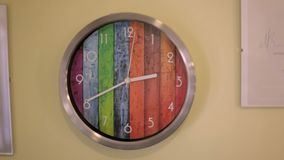 Wall clock on a beige wall. Wall clock multicolored stylized under the palette in the beauty salon stock footage