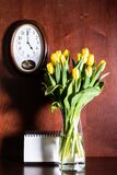 Wall clock, blank calendar and tulips in vase