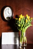 Wall clock, blank paper and tulips in vase