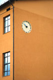 Wall clock on a building. Simple outdoor clock on a yellow apartments building wall in Jelgava city, Latvia Stock Photo