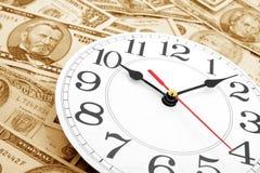 Wall clock and dollars Stock Photo