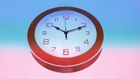 Wall clock giving 10 o`clock time hung on wall round orange borders