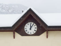 Wall clock with Roman numerals marking  five minutes after noon. Wall clock with Roman numerals, on the facade of an old house in the mountains, marking  five Stock Photo