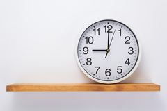 Wall clock at shelf on white background. Wall clock at wooden shelf on white background stock photography