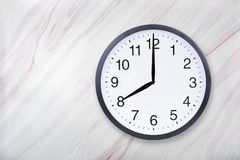 Wall clock show eight o`clock on marble texture. Office clock show 8pm or 8am royalty free stock photography