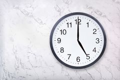Wall clock show five o`clock on white marble texture. Office clock show 5pm or 5am. On marble background royalty free stock photos