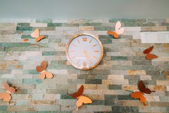 Wall clock in silver color on a brick wall. With butterflies Stock Photography