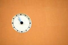 Wall clock. Simple outdoor clock on a urban building wall Stock Photos