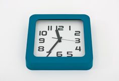 Wall clock. A stylish decorative wall clock hanging from a white wall Royalty Free Stock Image