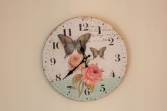 Wall clock. Time for wall clock. Clock hung over the wall. Old wall clock with rose and butterflies. Indoor home related Royalty Free Stock Photography