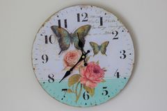 Wall clock. Time for wall clock. Clock hung over the wall. Old wall clock with rose and butterflies. Indoor home related Stock Photography