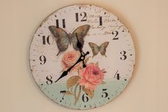 Wall clock. Time for wall clock. Clock hung over the wall. Old wall clock with rose and butterflies. Indoor home related Royalty Free Stock Photos
