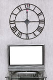 Wall clock under blank white screen of TV set Royalty Free Stock Photos