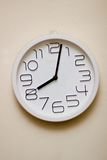 Wall Clock. White wall clock in a beige colored wall Stock Images