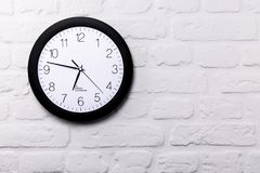 Wall clock on white brick wall. With copy space Stock Photography