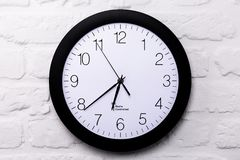 Wall clock on white brick wall. Full frame, closeup Stock Photos