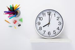 Wall clock at wooden shelf and school accessories. On white background royalty free stock image