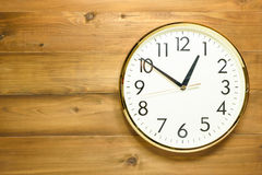 Wall clock on the wooden wall. Early afternoon Stock Photography