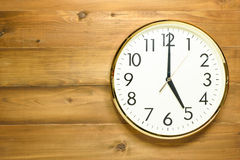 Wall clock on the wooden wall. At 5am or 5pm Royalty Free Stock Photo