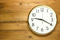 Wall clock on the wooden wall. At time 9am or 9pm Stock Images
