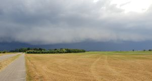 Wall cloud of a thunderstorm above dry yellow fields and green trees in Laag Zuthem in Overijssel, the Netherlands. Wall cloud of a thunderstorm above dry stock images