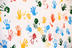 Wall with colored prints of human hand Stock Photo