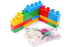 Wall of colorful building blocks with home keys and money. Wall of plastic colorful building blocks with home keys and banknotes, concept for building home Stock Photo