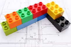 Wall of colorful building blocks on housing plan. Wall of colorful building blocks lying on construction drawing of house Royalty Free Stock Photos