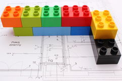 Wall of colorful building blocks on housing plan. Wall of colorful building blocks lying on construction drawing of house, concept for building house Stock Images