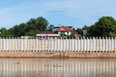 Wall of concrete pillars blocking the river. Many concrete pillars are installed as walls to protect the river from eroded coastal waters near homes Stock Photos