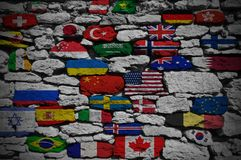 Wall consisting of stones painted in different flags of the world. Close-up stock photo